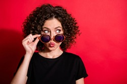 Photo portrait of pouting girl taking of glasses looking at blank space isolated on vivid red colored background