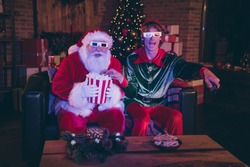 Photo portrait of santa claus and elf eating popcorn using remote watching movie on sofa in 3d glasses