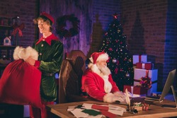 Photo portrait of santa claus working on desktop and elf carrying big red gift bag