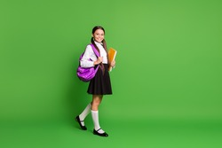Photo portrait of schoolgirl going forward holding books in hand wearing violet backpack on shoulder isolated on vivid green colored background with copyspace