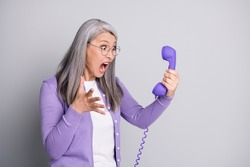 Photo portrait of senior mad furious stressed woman shouting screaming loudly keeping handset of retro violet phone with wire isolated on grey color background