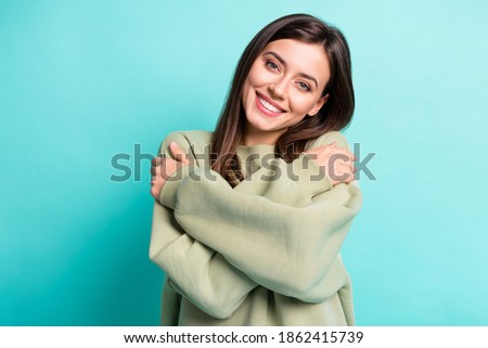 Photo of  Photo portrait of smiling girl hugging self isolated on vivid cyan colored background