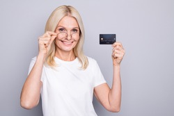 Photo portrait of smiling old lady taking off glasses holding credit card in one hand isolated on grey colored background