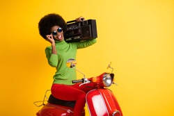Photo portrait of stylish biker driving red motorbike holding boombox touching glasses isolated on vivid yellow colored background