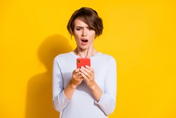 Photo portrait of upset girl holding phone in two hands isolated on bright yellow colored background