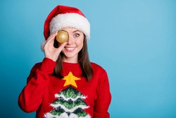 Photo portrait of woman holding golden christmas bauble near eye isolated on pastel light blue colored background with copyspace