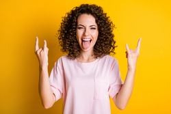 Photo portrait of woman showing tongue making two rock goat signs isolated on vivid yellow colored background