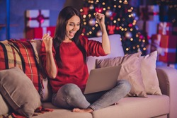 Photo portrait of woman sitting on sofa in lotus pose with laptop celebrating victory with fists in air with christmas decorations indoors