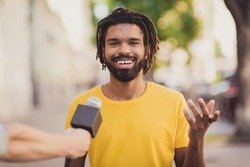 Photo portrait of young man smiling giving interview to journalist talking in microphone on street