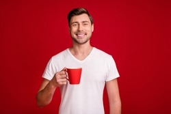 Photo portrait of young smiling guy keeping cup of coffee on break isolated vibrant red color background