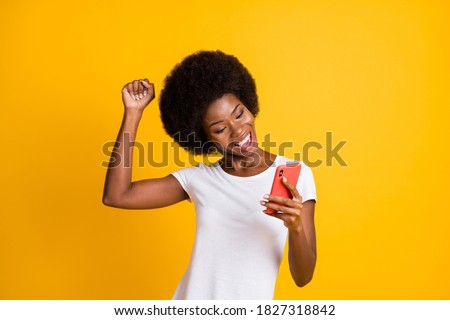 Photo portrait of young woman celebrating victory holding one fist up wearing casual white t-shirt isolated on vivid yellow colored background