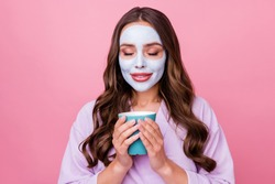 Photo portrait of young woman with wavy brown applied moisturizing facial mask chilling relaxing keeping cup of hot tea isolated on pink color background