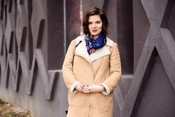 Photo portrait walk brunette girl in a beige coat in the city in sunny weather is standing against a dark purple wall of a building