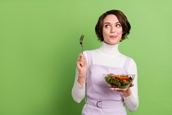 Photo portrait woman keeping salad hungry looking copyspace isolated pastel green color background