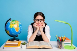 Photo positive a-level high school student girl sit table read geography globe textbook enjoy academic courses wear white blouse black overall uniform isolated blue color background