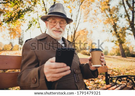 Photo positive modern old man pensioner enjoy autumn forest break pause rest park use smartphone typing email sit bench drink hold takeout coffee mug wear coat jacket hat cap headwear Сток-фото ©