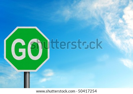 Photo realistic metallic reflective 'Go' sign, against a bright blue sunny summer sky. With space for your text / editorial overlay