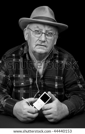 photo senior male listening to mp3 music player