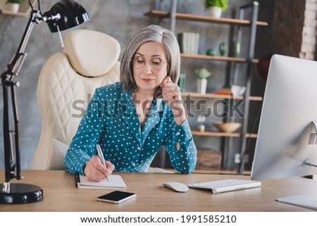 Photo serious calm old pretty grey haired woman wear glasses write note manager look indoors in workplace workstation Foto stock ©