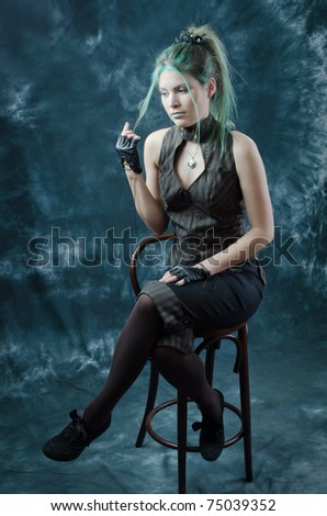 Photo session of the pretty young blonde girl with green hair in the steampunk style