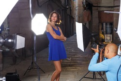 Photo shoot of young brunette model with professional photographer on evening city street