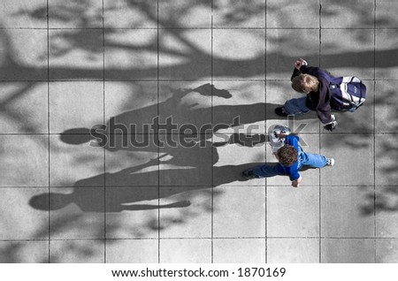 Photo shot from above of two schoolboys walking along a city street.