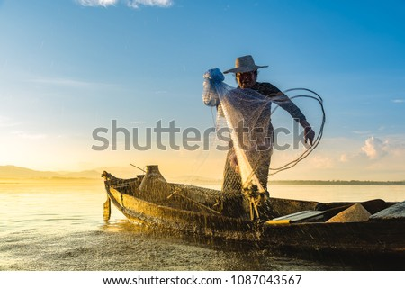 Photo shot of water spatter from fisherman while throwing fishing net from boat. Silhouette of asian fishermen with fishing net in morning sunshine along harbor. Stop motion water drop on sea.