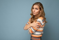 Photo shot portrait of young nice winsome beautiful sad upset sorrowful deplorable blond woman with sincere emotions wearing striped sweater isolated over blue background with free space