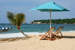 Photo shows Atlantic Ocean beach. Caribbean coastline has yellow sand. Loungers for relaxation and sunbathing are visible. In addition to sun loungers, there are also umbrellas that protect from sun.