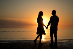photo silhouette of a love couple. sunset, lake, romantic. portrait of a young woman and a man beach.