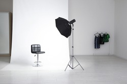 Photo studio interior with modern chair and professional lighting equipment
