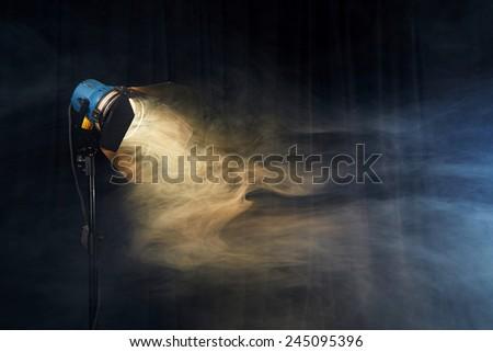 Photo studio lighting equipment on black background with smoke