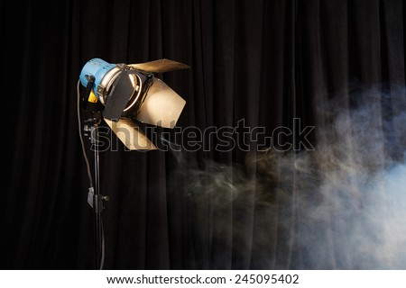 Photo studio lighting equipment on black background with smoke