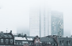 Photo stylised by old with grain: view to the Frankfurt city centre by fog, modern skyscrapers and old building foreground