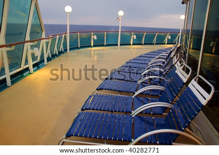 photo sunset evening lounge chairs in a row on a ocean cruise ship