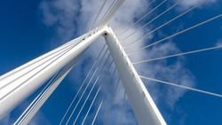 Photo taken of the top spire of the Northern Spire bridge in Sunderland, showing cables and the white metal structure against the blue sky.