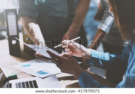 Photo team work process,holding contract hand,signs documents. Account managers young crew works with startup project.New idea presentation, analyze marketing reports. Blurred, film effect, horizontal