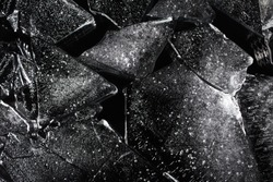 Photo texture of a black and white ice laying on dark background.