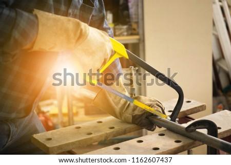 Photo to worker use hacksaw cutting metal pipe.