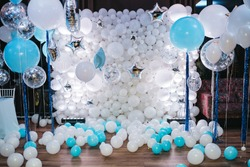 Photo-wall of white balloons and blue and silver balloons hanging before it in a dark dining hall