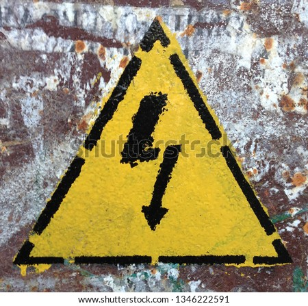 Photo warning sign of high electrical voltage. Yellow Sign of lightning in the triangle on the background of a rusty dirty surface.