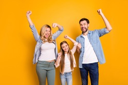 Photo wife beautiful mother lady husband dad guy couple little school girl daughter happy raise fists win competition one team wear casual shirts clothes isolated yellow color background