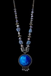 photo with art vintage old decorative Indian style jewellery neckless in silver metal with round chain and main part in spherical shapes with big and small blue stone balls on black background