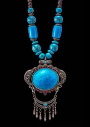 photo with art vintage old decorative jewellery necklace in bronze metal with blue stones chain, main part in spherical shape with big blue stone ball with decorative small metal parts on black back