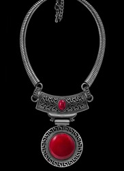 photo with art vintage old decorative jewellery neckless in silver metal with round chain and main part in spherical shapes with big and small red stone balls on black background