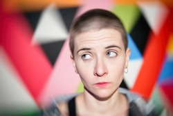 Photo with Blur effect. Close-up portrait of young emotional woman with short hair on bright geometric background