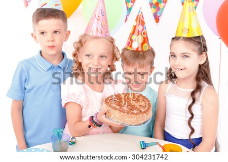 Photo with cake. Little birthday girl holding cake and posing with her smiling friends to camera.
