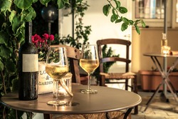 Photo with evening light. Misted  glasses with white wine and bottle on the table. Outside bar terrace. Cafe concept. Selective focus.