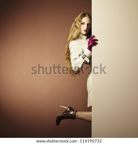 Photo young beautiful woman in a raincoat in interior. Conceptual fashion