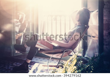 Photo young girl sitting leather armchair in modern building and use laptop wireless internet. Studying at the University, working, preparing exams. Using book, notebook. Sunny day. Horizontal